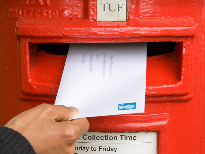A woman's hand is shown posting an envelope into a bright red postbox.