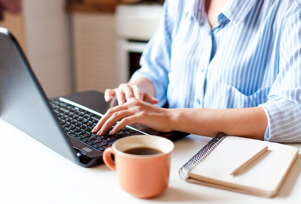 Freelancer  in a blue and white pinstripe shirt at her workplace with laptop, cup of coffee and notebook.